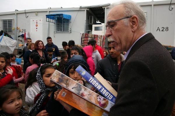 希臘移民部長特薩斯(Dimitris Vitsas,圖右)到國內難民營發新年禮物給難民小朋友們。(歐新社)