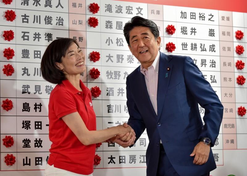 本次日本參議院改選,女性當選人創下史上最高人次。圖為首相安倍晉三與女性當選人丸川珠代握手照片。(法新社)