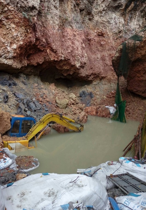 壽山挖寶計畫現場因連日大雨嚴重積水,怪手也陷在水中。(讀者提供)