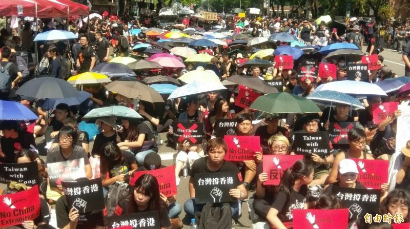參與的人們高舉標語,包括紅底的「反送中」、黑底紅叉的「拒絕一中、拒絕和平協議」、與黑底白拳頭圖樣的「台灣撐香港」,高喊「撐香港,反送中!」(記者劉信德攝)