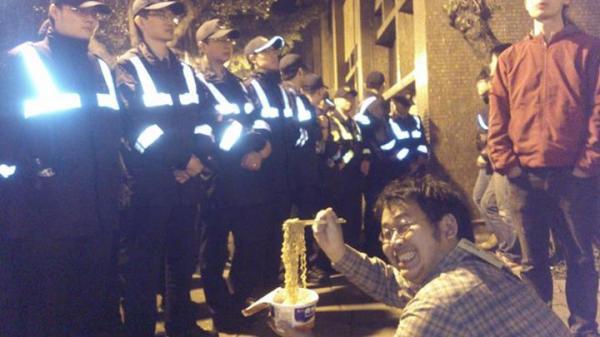 面對站崗的警察,有鄉民KUSO了一張照片,照片中的男子路出詭異笑容,並在排排站的警察面前吃起維力炸醬麵,讓眾多網友直呼這才是真正的暴民!(照片擷取自網路)