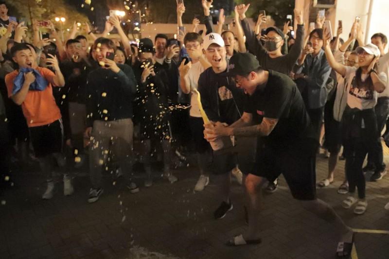 支持民主的支持者在得知何君堯在選舉中失利,高興慶祝的場景。(美聯社)