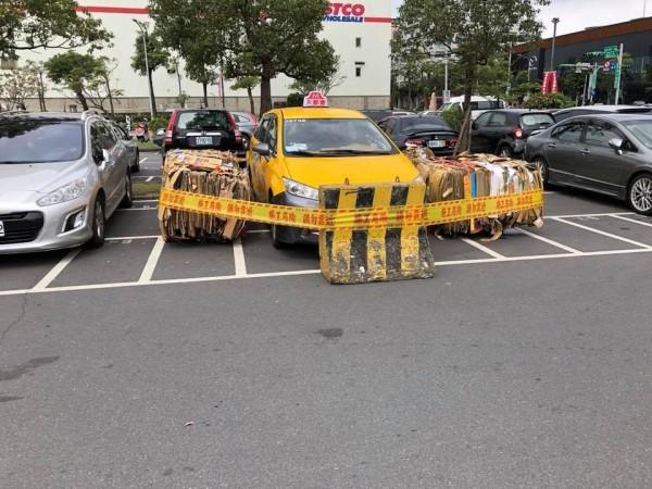 一輛計程車自作聰明在大賣場停車場過夜,沒想到被賣場人員用紙箱與護欄「包圍」起來。(圖擷自臉書社團「爆廢公社」)