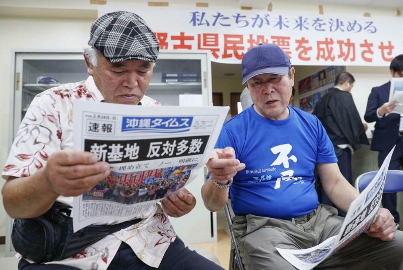沖繩縣當地居民對駐日美軍非常不滿,圖為「是否贊成駐日美軍普天間基地遷徙」公投案隔日,當地居民閱讀開票結果。(美聯社)