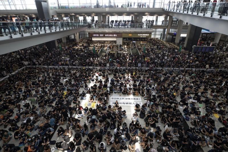 香港網友12日下午發起「警察還眼」行動,群眾塞爆香港機場,晚間6點起所有航班取消。(美聯社)