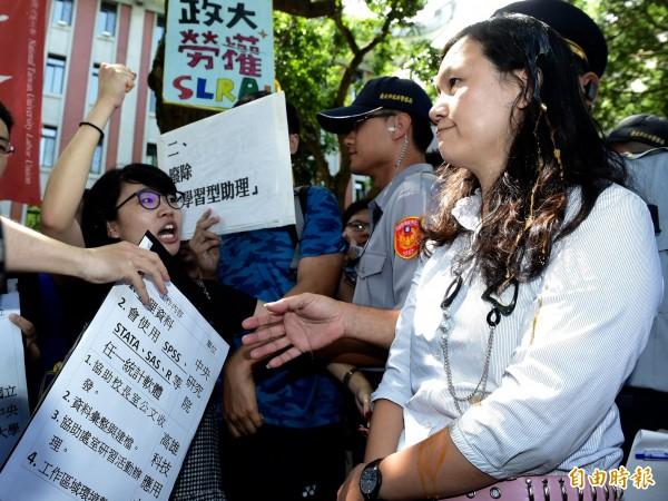 台灣高等教育產業工會、台灣大學工會等勞團代表,4日在教育部大門口聯合行動記者會,要求廢除「學習型助理」、還我勞健保。代表教育部出面的高教司專員王淑娟(右)遭學生爆蛋抗議。(資料照,記者簡榮豐攝)