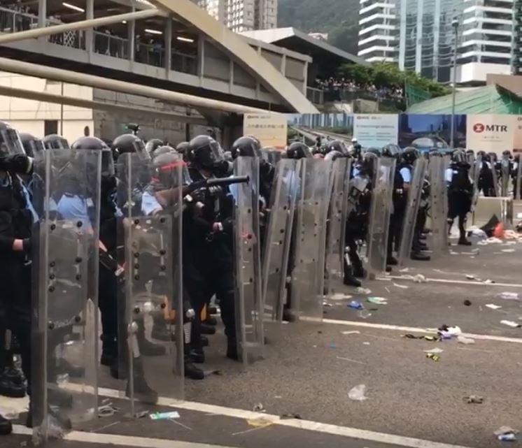 警方手持盾牌排成一列,中間有1名警察準備朝示威群眾發射催淚彈。(圖擷自香港電台視像新聞 RTHK VNEWS)