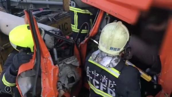 電桿硬生生插入後方物流車頭,消防人員動用油壓剪等器具終於將受困凹陷車頭內的駕駛及副手救出,所幸送醫時意識清醒、沒有生命危險。(台中市消防局提供)
