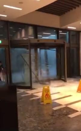 旋轉門因颱風而高速旋轉,玻璃應聲破裂,吸引不少網友觀看。(圖擷取自陳泰霖臉書影片)