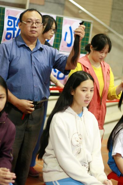家長為學生剪下頭髮捐助癌症患者。(記者劉彥甫攝)