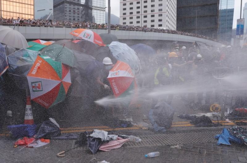香港警方對抗議民眾發射催淚瓦斯壓制,民眾展開雨傘防衛持續進擊。(路透)
