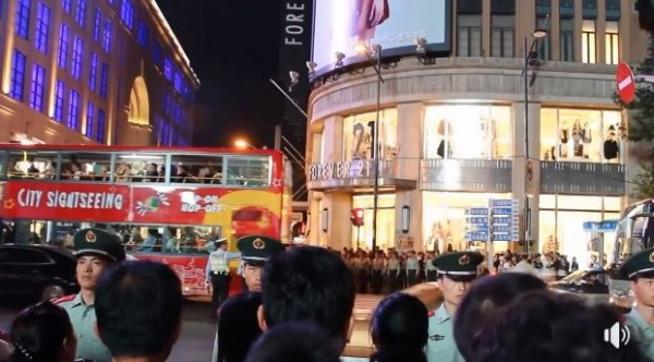 在行人穿越號誌為紅燈時,武警們一字排開擋在人群與道路之間。(圖擷取自微博)