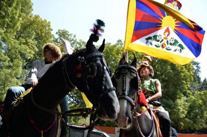 西藏抗暴運動60週年,世界各地的支持者聚集西藏流亡政府所在地、印度北部山區的達蘭薩拉,搖著被中國政府禁止的西藏「雪獅旗」舉行紀念活動。(法新社)