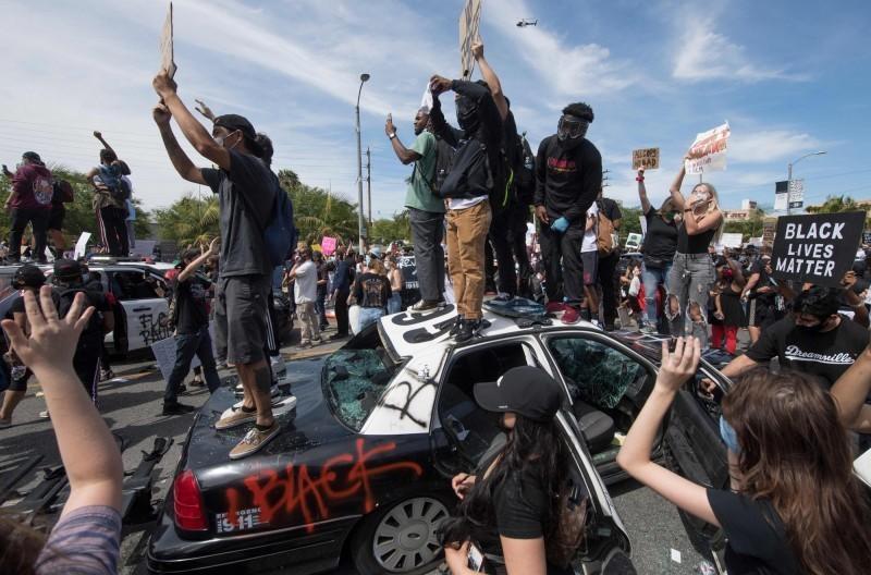 旅美台灣網紅「小商人」回憶20多年前洛杉磯暴動場景,當時為了防止「越青、黑人幫派與老墨幫派」等人打劫,與朋友共6人守在店裡3天,「有人敲玻璃要進來就先開槍」,最後成功沒讓黑幫暴徒洗劫財物。圖為近日示威活動中,洛杉磯有示威群眾將多輛警車砸毀。(法新社)