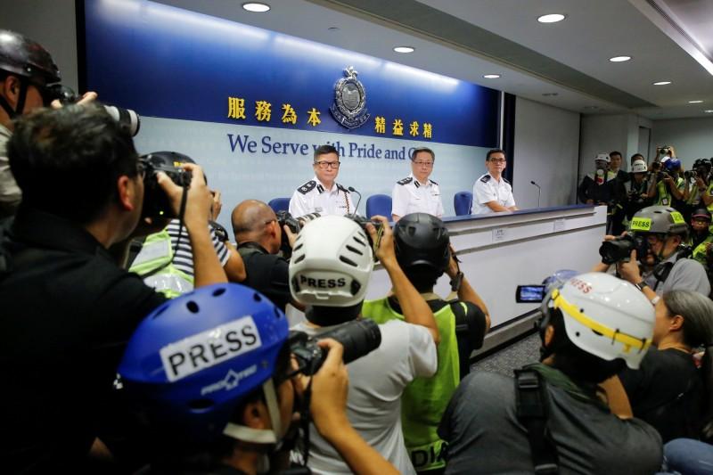 香港警務處處長盧偉聰(中)昨天先是稱抗爭行動為「騷亂」,而後又發新聞稿改稱「暴動」,盧偉聰今天則說,此為英翻中的疏失,他的原意是「暴動」。(路透)