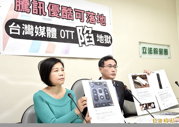 Democratic Progressive Party legislators Yeh Yi-jin, left, and Cheng Yun-peng display information about video streaming services by Tencent Holdings and Youku Tudou at a news conference at the Legislative Yuan in Taipei yesterday. Photo: Chien Jung-fong, Taipei Times