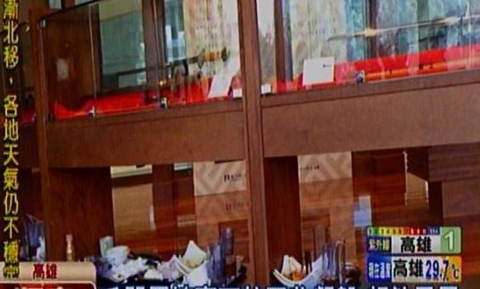 「冷兵器藝術系列特展」,上面櫥窗展出琳瑯滿目的兵器,下方竟堆滿了油膩膩的餐盤。(圗擷取自東森新聞)
