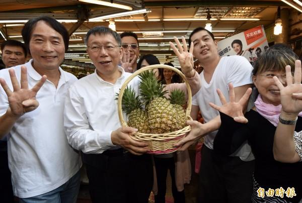 台北市長柯文哲(左二)15日前往內湖路一段737巷掃街,向攤商、民眾拜票,民眾送上鳳梨等預祝當選。(記者簡榮豐攝)