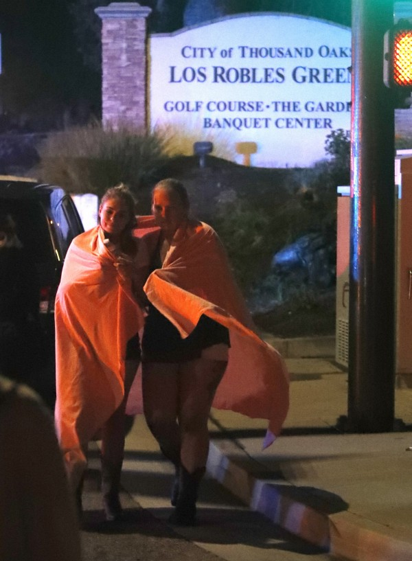 2名女子餘悸猶存,裹著毯子從酒吧離開。(法新社)