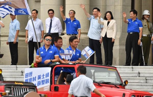 吉普車、大巴士載著選手們,從總統府前凱達格蘭大道出發,總統蔡英文(後右3)向選手們揮手致意。(中央社)