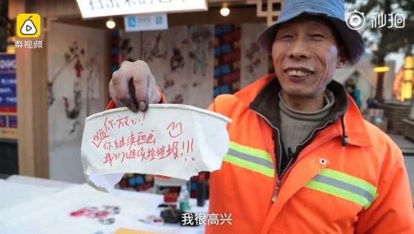 高亞軍收到一名遊客在杯子上寫「以後你繼續畫,我們繼續撿垃圾」的留言,讓他相當感動。(圖擷取自梨視頻)