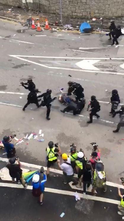 可以看到影片中的警察全副武裝圍毆1名示威民眾。(圖擷自爆廢公社)