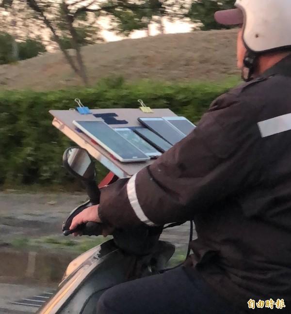 寶可夢迷莊姓男子在機車上架設板子,一次擺放5支平板和行動電話,穿梭在大街小巷,方便抓寶、打道館。(記者廖雪茹攝)