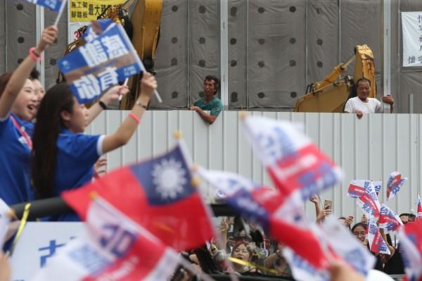 館前路旁的工地工人,也攀上圍籬,一睹台灣隊選手的風采。(中央社)