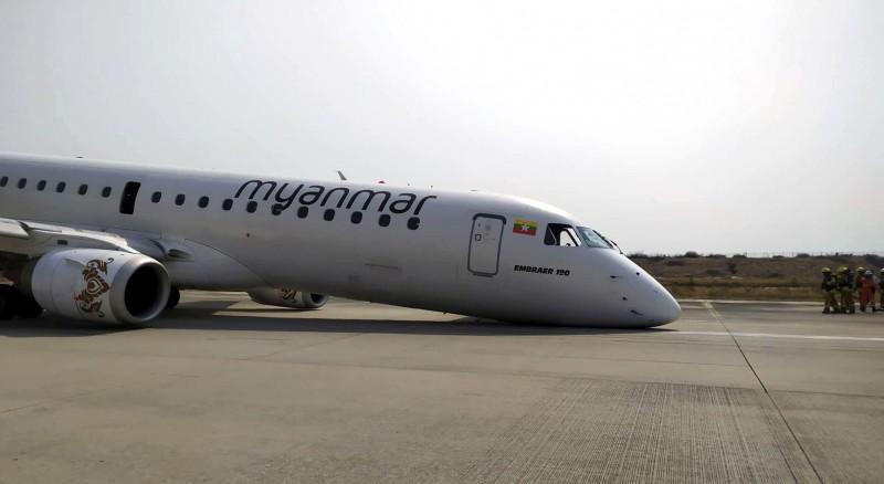 緬甸國家航空的這架班機,由於起落架故障導致前輪無法放下,最終以機鼻和後輪成功迫降於機場跑道上。(美聯社)