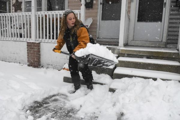 紐約市民忙著清理屋外積雪。(美聯社)