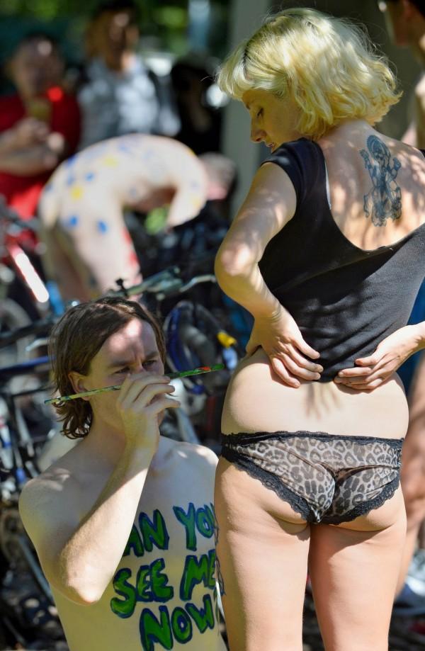 有不少單車騎士在身上畫上不同的圖畫及宣傳標語,只戴安全帽全裸上路。(法新社)