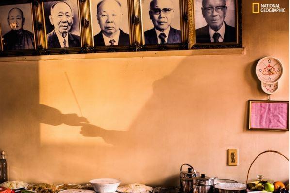 洪勗桔表示,「薪火相傳」這張照片是2015年農曆新年時,在他位於台中沙鹿的老家所拍攝,當時他家裡的長輩把香遞給晚輩,開始祭祖祈福,他注意到光線正好透進房間,於是拍下這張照片。(圖擷取自《國家地理雜誌》網站)