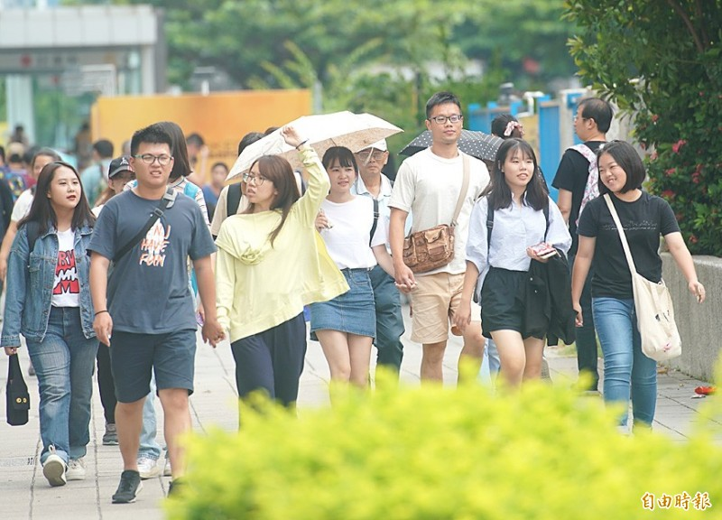 Some women use umbrellas as parasols in Kaohsiung yesterday. Photo: Huang Chih-yuan, Taipei Times