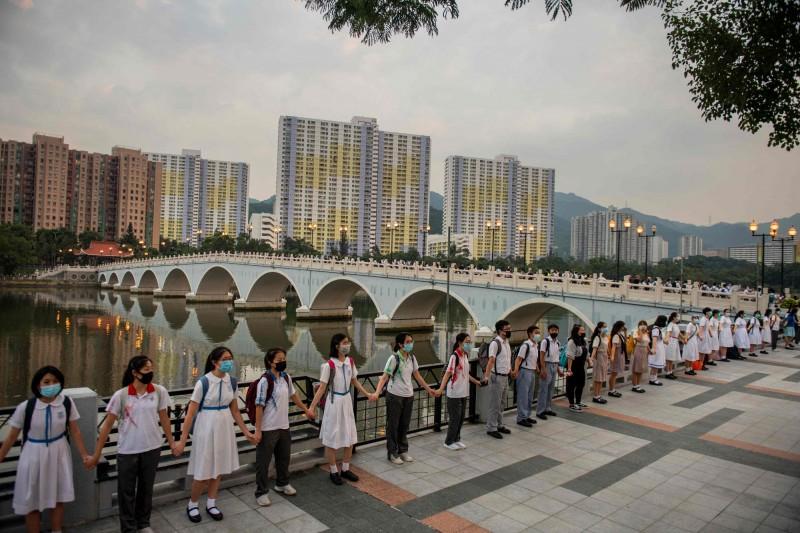 沙田區學生19日發起人鏈活動,重申反送中5大訴求,而學生組織「學生動源」此前在轉發消息時,提到香港特區政府未實行雙普選,已嚴重違反《中英聯合聲明》。(法新社)