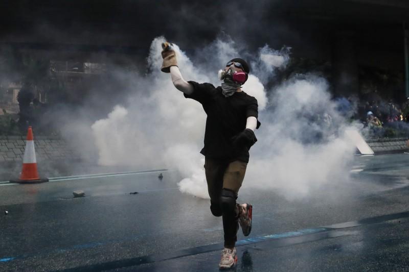 示威者擲回警方發射的催淚彈。(歐新社)