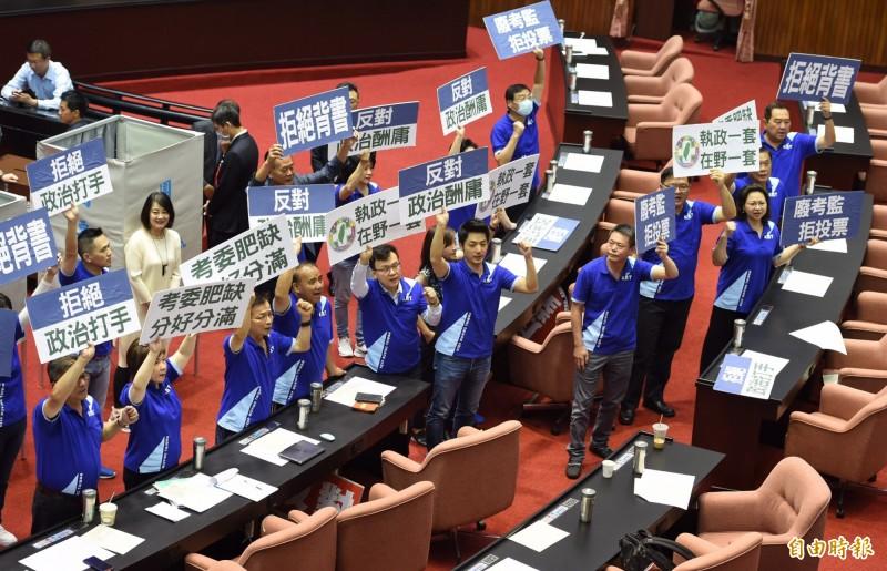 國民黨立委進入議場,並手持標語高呼口號,強調反對政治酬庸、拒絕背書。(記者劉信德攝)