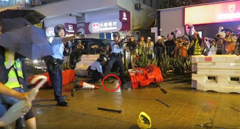 香港825遊行警方首次開槍,事後解釋是現場警員遭受「生命威脅」不得已為之,但有真正原因疑似警員自己「掉槍」落漆。(圖擷取自粉專「SocREC 社會記錄頻道」影片)