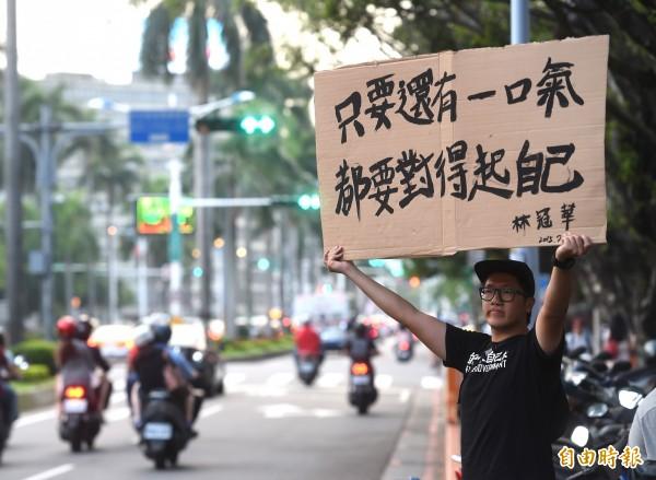 反課綱學生燒炭輕生,民眾在教育部前舉海報表達訴求。(記者方賓照攝)