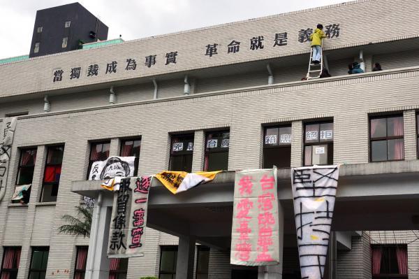反黑箱服貿佔領立法院活動持續,今天下午議場外牆被前民進黨主席施明德的大女兒施蜜娜噴上「當獨裁成為事實,革命就是義務」的大字。(記者鹿俊為攝)