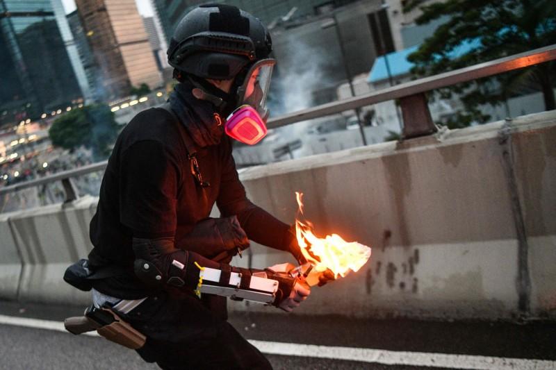 法新社記者拍到一名「示威者」丟擲汽油彈的照片,卻被香港網友揭發,其腰際的配槍是港警常用的「Glock 19」。(法新社)
