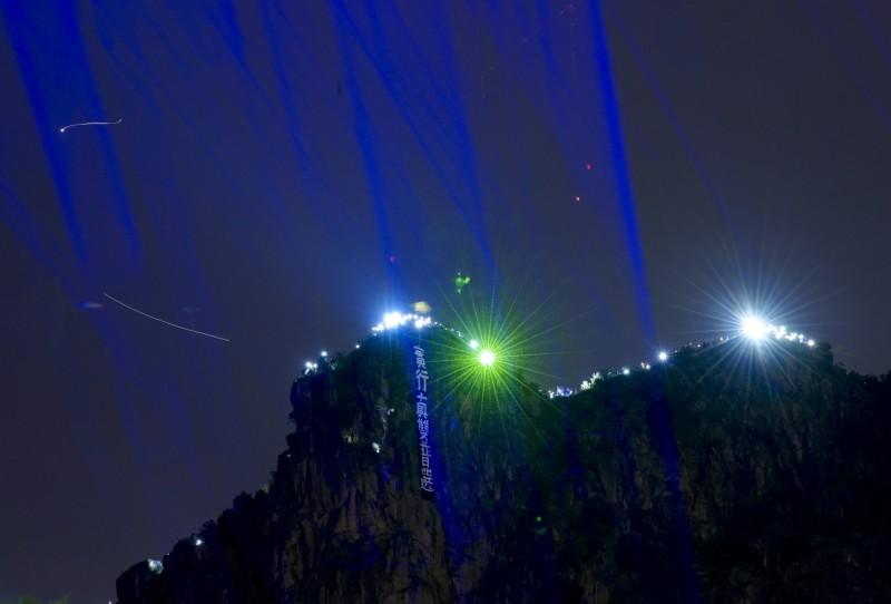 香港市民發起築人鏈行動,聚集在獅子山,並高舉手機或雷射筆點亮山峰。(美聯社)