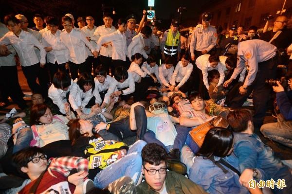 黑色島國青年陣線等年輕人今晚(31日)間為抗議申請亞投行,晚間試圖衝撞總統府,隨即被憲兵及維安人員攔阻。(記者王藝菘攝)