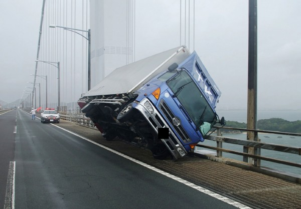 日本四國地區的貨車不敵強風,整輛車傾倒在路邊。(法新社)