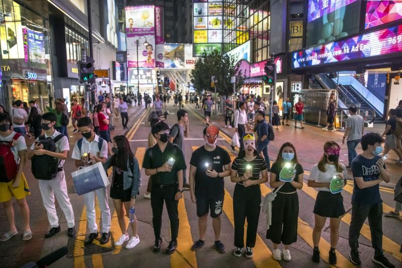 示威者不時亮起手機燈、高喊口號表達訴求,「蒙面無罪、立法無理!」、「我有權戴口罩」。(美聯社)
