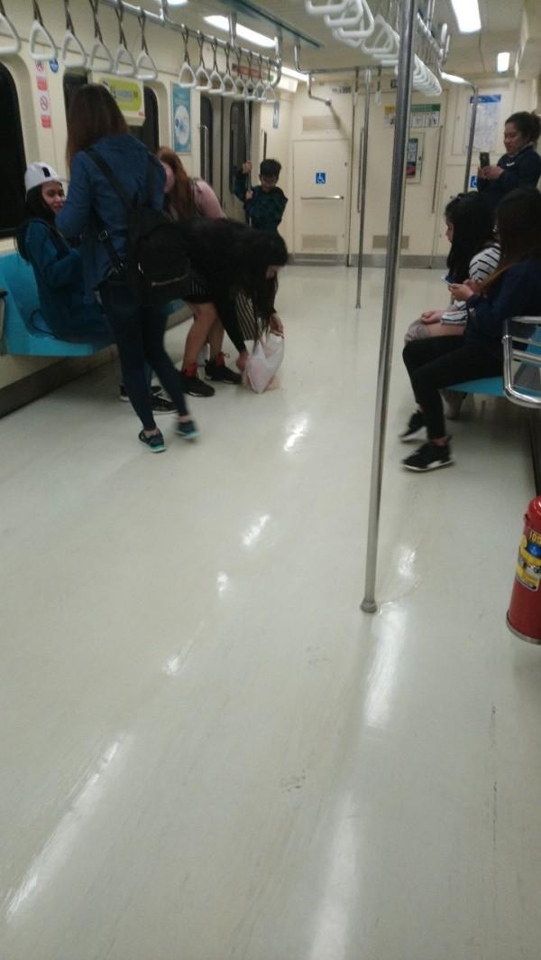 外籍旅客用「圍巾」將列車地板的奶茶漬擦乾淨後才下車。(圖擷取自PTT)