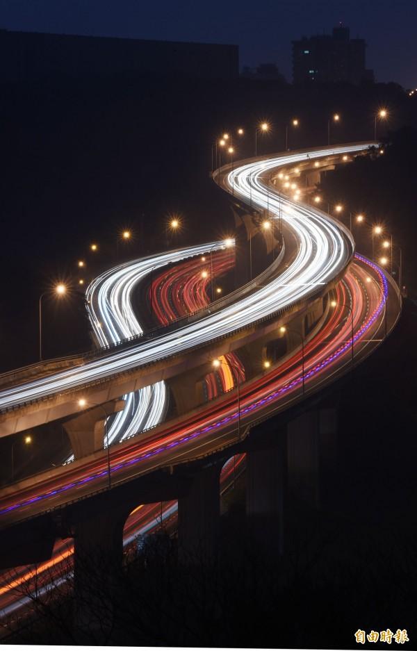 圖為春節期間高速公路湧現返鄉車潮,車燈的軌跡在高速公路上劃出一道道光。(資料照,記者王敏為攝)