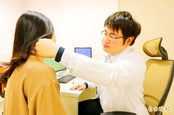 Asia University Hospital Department of Infectious Diseases attending physician Chang Wei-shuo, right, examines a patient at the hospital in Taichung on Dec. 20. Photo: Chen Chien-chih, Taipei Times