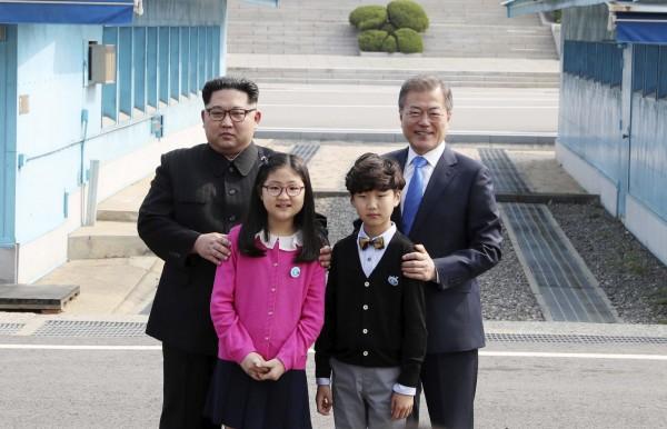 來自兩韓非軍事區、南韓方唯一村莊的一對男女花童,負責一起獻花給金正恩。並與金正恩還有文在寅一起合照。(美聯社)