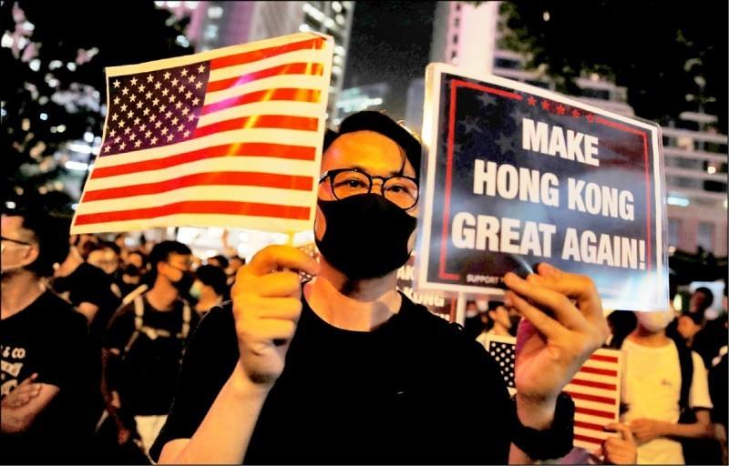 美國聯邦眾議院15日通過香港民主抗爭者力爭的「香港人權與民主法案」。前一晚有13萬名港人集會,一名參與者一手持美國國旗,一手拿著「讓香港再次偉大」標語,為美國國會通過此法案「集氣」。(路透)