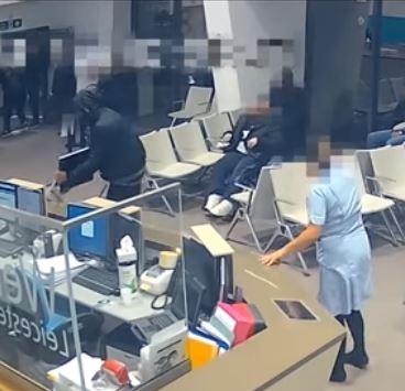 阿卡(左)狂砸醫院電腦,一名坐輪椅的病患(中)為了逃離現場,不得已經過阿卡身邊。(圖擷取自Youtube「 Leicestershire Police」)